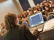 Image of a person presenting at a conference