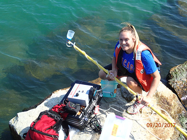 Intern Samantha Jurecki collecting a water samples at Washington Park Beach